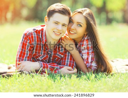 Portrait happy young couple having fun smiling lying on the grass in summer sunny day - stock photo