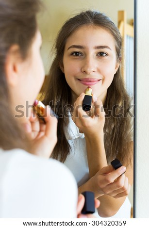 Portrait happy young girl admiring himself in front of the mirror - stock photo