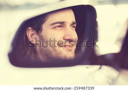 Portrait happy young man driver reflection in car side view mirror. Guy driving his new car. Positive human face expression emotions. Safe trip journey driving concept - stock photo