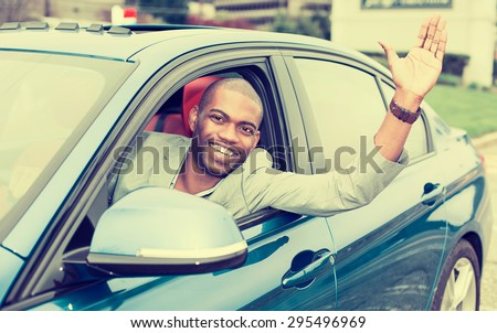 Portrait happy young man driver stuck his hand out of the car window excited about his new blue car - stock photo