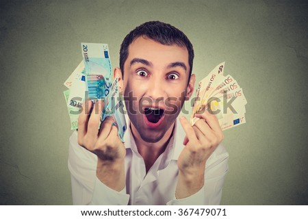 Portrait happy young man with money euro banknotes ecstatic celebrates success screaming isolated on gray background. Financial freedom achievement concept - stock photo