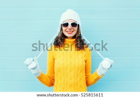Portrait happy young smiling woman wearing a sunglasses, knitted hat, sweater over blue background