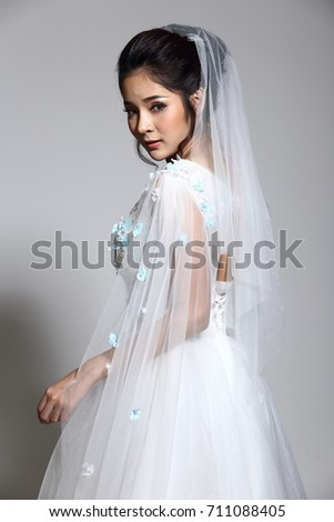 Portrait Head shot, Lovely Asian Beautiful Woman bride in white wedding gown dress with lace, black hair, studio lighting grey background, isolated copy space, sweet romantic soft alone concept