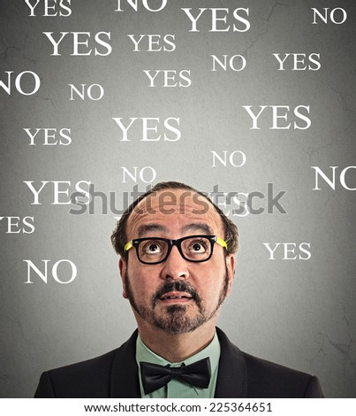 portrait headshot undecided business man looking up grey wall background with yes no choices text. Human face expression, emotions, feelings. Decision making life choice process concept - stock photo