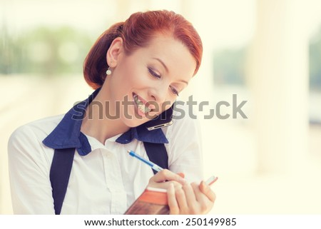 Portrait headshot young happy smiling woman talking on mobile phone taking notes outside corporate office building isolated city background. Positive human face expression emotion life success concept - stock photo