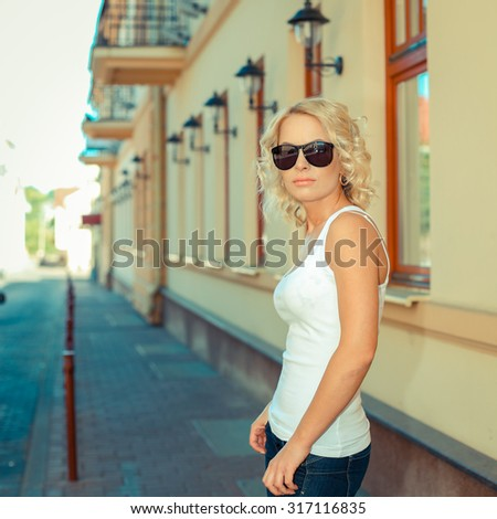 Portrait hipster blonde girl in casual clothes. Portrait of fashionable blonde girl with red lipstick having fun outdoors in the city