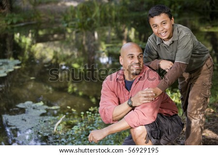 Portrait Hispanic father and son outdoors by pond enjoying nature
