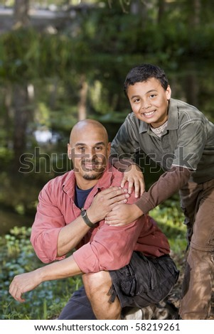 Portrait Hispanic father and son outdoors by pond enjoying nature - stock photo