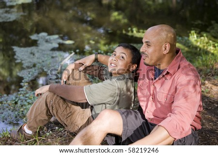 Portrait Hispanic father and son outdoors by pond having conversation - stock photo