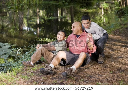 Portrait Hispanic father and sons outdoors by pond having conversation - stock photo