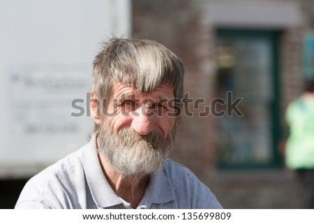 Portrait homeless man with beard outdoors during the day - stock photo