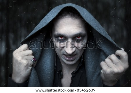 Portrait horrible fashion male vampire (demon or evil wizard)  knocking to rainy and misted window. Halloween concept - stock photo