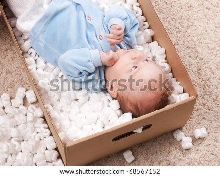 Portrait if cute newborn baby lying in open post box with filler on carpet. Small baby resting in package and smiling for parents. - stock photo