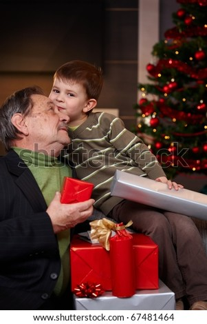 Portrait if happy grandfather and grandson holding christmas presents, cuddling. ? - stock photo