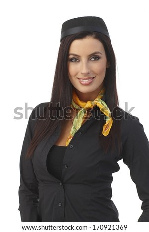Portrait if pretty young stewardess with long hair wearing hat, smiling, looking at camera. - stock photo