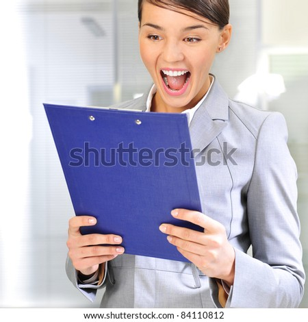 Portrait if young business woman at her office holding report