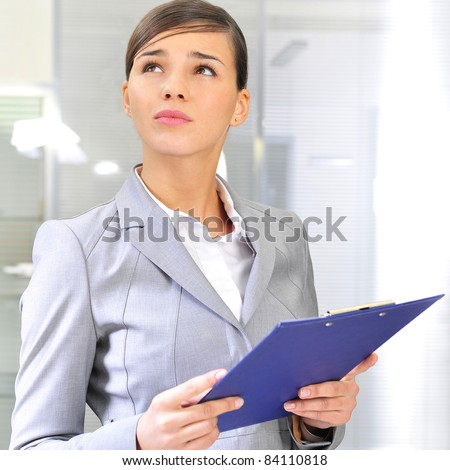 Portrait if young business woman at her office holding report - stock photo