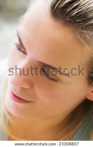Portrait image of a beautiful young woman looking pleased, in the morning light - stock photo
