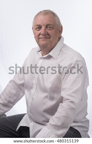 Portrait image of a mature man sitting down. Taken on a white background.