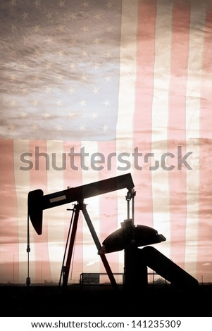 Portrait image of a oil well pumpjack wiith early morning light and American USA red White and Blue Flag background. A Pumpjack is the overground drive for a reciprocating piston pump in an oil well. - stock photo