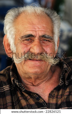 Portrait image of a senior Greek male with a big mustache looking at the camera