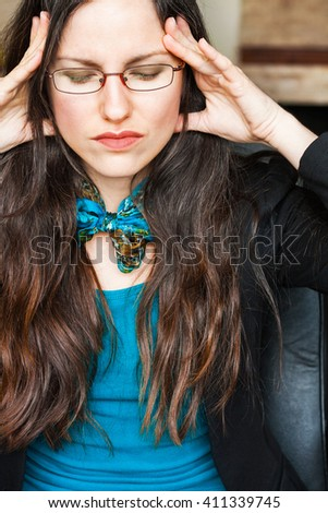 Portrait image of a young business woman suffering from pain, holding her head.  - stock photo