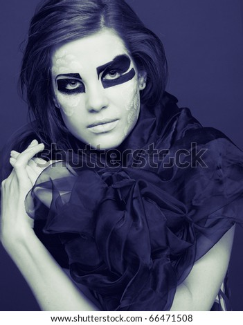 Portrait in cold tones. Young woman in black scarf with original  creative make-up - stock photo