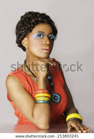 Portrait in color of beautiful African woman in bright orange dress, wearing necklace, earrings and bangles, posing with her head on her hand - stock photo