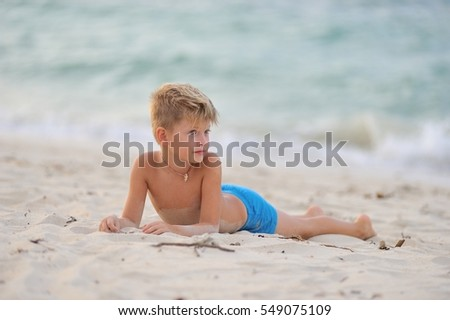 Portrait in full growth: blue eyed blonde 8 years old handsome boy dressed in blue shorts. Boy lying in the sand by the sea
