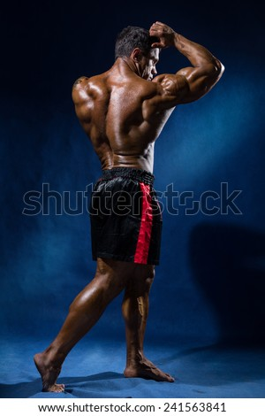 Portrait in full growth bodybuilder. Looking away and shows his biceps - stock photo