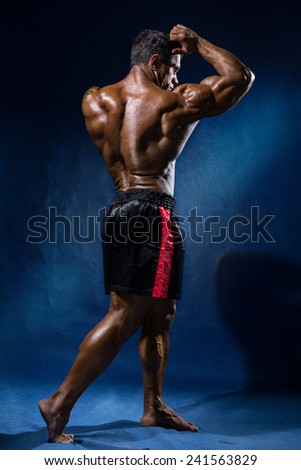 Portrait in full growth bodybuilder. Looking away and shows his biceps on a blue background - stock photo