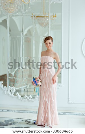 Portrait in full growth gentle sensual beautiful blonde bride in a pink dress and veil with a bouquet of flowers in his hands, a bright interior - stock photo