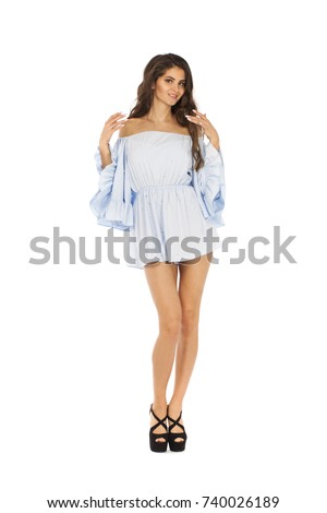 Portrait in full growth of a beautiful young brunette woman in blue dress, isolated on white background