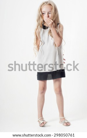 Portrait in full growth of happy little girl with long curled hair covers her mouth with her palm - stock photo