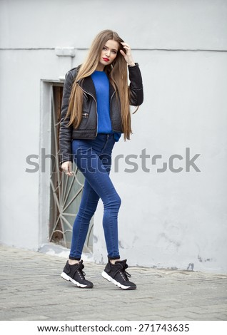 Portrait in full growth the young beautiful girl in blue jeans and a black leather jacket on the background of spring street - stock photo