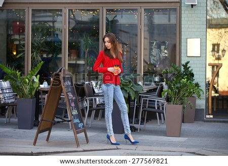 """Portrait in full growth the young beautiful girl in blue jeans and red shirt. The inscription on the board in Russian: """"Business - Lunch"""", """"12 to 16"""", """"390 rubles"""", soup, salad, main dish """" - stock photo"""