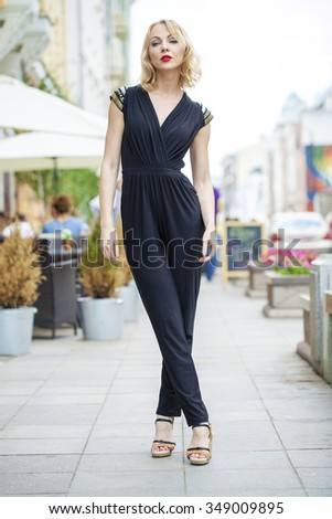 Portrait in full growth, Young beautiful blonde woman in black dress posing outdoors in sunny weather