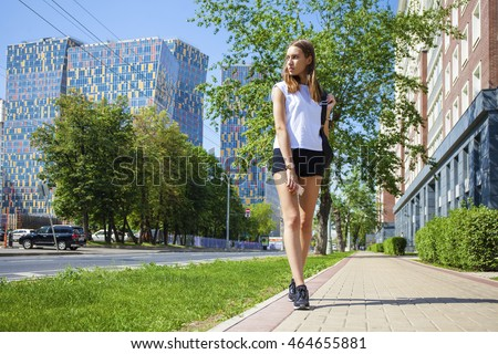 Portrait in full growth, young beautiful brunette woman in black short walking on the street, summer city outdoors