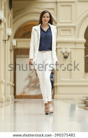 Portrait in full growth, young beautiful brunette woman in white coat walking in the mall - stock photo