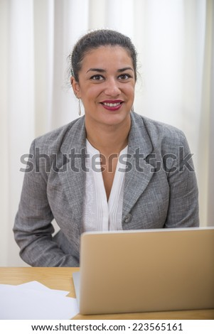 Portrait in office of businesswoman head and shoulders sitting behind her laptop computer on wood desk. She is smiling. - stock photo