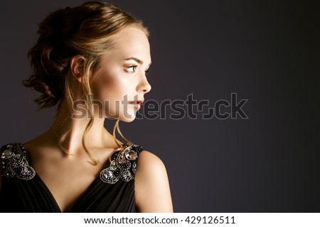 Portrait in profile of a beautiful girl with an evening make-up and hairstyle. Beauty, fashion. Studio shot. - stock photo