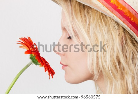 Portrait in profile of a pretty blonde woman with closed eyes smelling a red flower. - stock photo