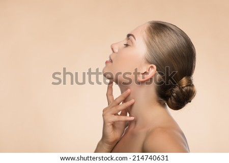 Portrait in profile of beauty face of beautiful girl with clean and  fresh skin with closed eyes touching her face isolated on beige background with copy place - stock photo