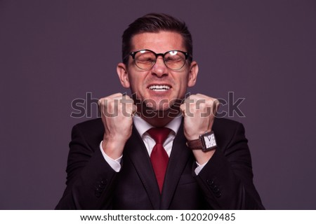 Portrait in purple tone Happy positive businessman in formal suit and glasses is happy and shouts Yes.