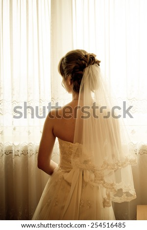 portrait in warm tone of a attractive woman in a bridal dress and veil near the window - stock photo