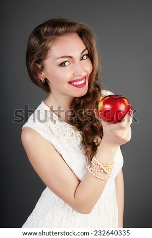 Portrait in white dress of girl with red apple. Beautiful pretty girl in studio.