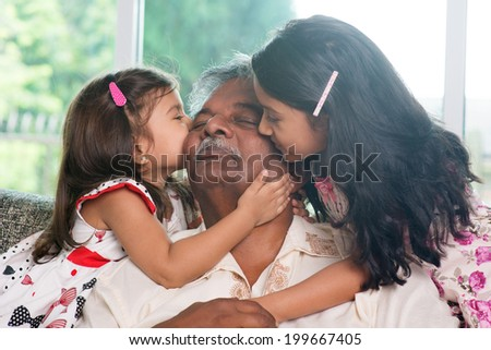 Portrait Indian family at home. Grandchildren kissing on grandparent face. Asian people living lifestyle. - stock photo