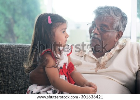 Portrait Indian family at home. Grandparent and grandchild talking together. Asian people living lifestyle. Grandfather and granddaughter. - stock photo
