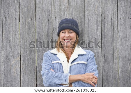 Portrait joyful confident smiling attractive mature woman outdoor, wearing warm bonnet and wool jacket, timber wall background, copy space. - stock photo