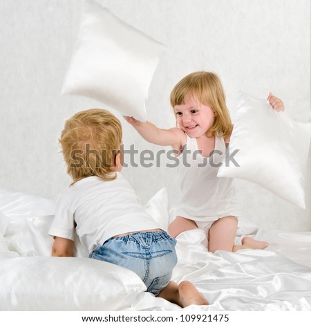 Portrait kids fighting with pillows in bed - Indoor - stock photo